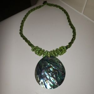 Green beaded necklace with abalone pendant